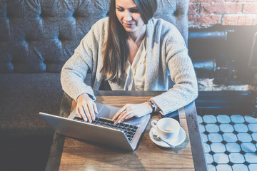 Young businesswoman with long hair sits at table in cafe and uses laptop.On table is cup of coffee.