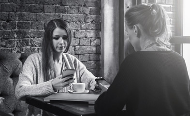 Black and white image. Two young women sitting in a cafe at the table and using smartphones.