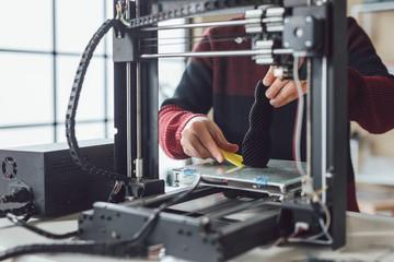 A men detaching new made object from 3d printer.