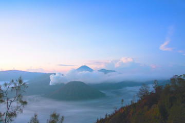 White smoke coming out of volcanoes surrounded by white clouds of mist and a clear blue sky seen at a distance in the afternoon at National Park in East Java, Indonesia.