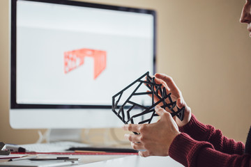 A man graphic designer doing quality control of object made on 3d printer.