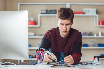 Young Caucasian man graphic designer using 3d printing pen at office.