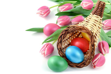Easter eggs with a cornucopia and bunch of pink tulips on isolated white background