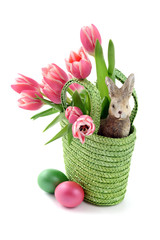 Easter eggs with a basket and bunch of pink tulips on isolated white background