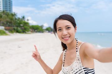 Woman taking selfie by mobile phone in beach
