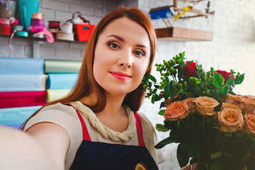 young girl working in a flower shop, Floristry makes selfie photo with a bouquet of flowers