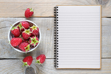 Raspberry and recipe book on wooden table