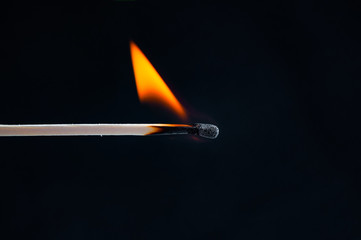Burning match closeup on black background