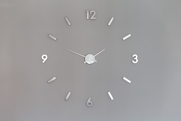Silver shiny clock numbers at the wall with copy space