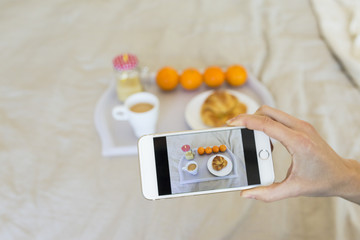 woman taking picture of  tray with breakfast on her smartphone. Top view