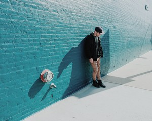 Man standing against turquoise painted brick wall
