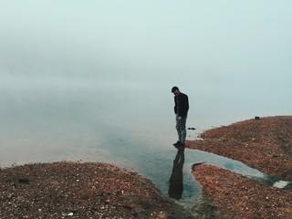 Man looking at reflection at waters edge