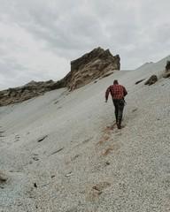 Man ascending sandy slope, rear view