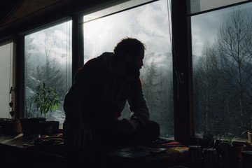 man contemplates winter view from cabin