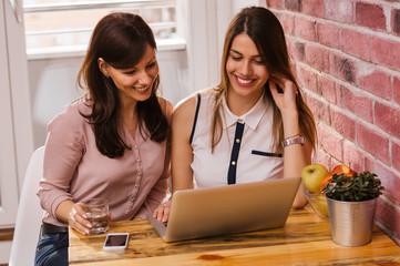 Two happy women friends watching social media on laptop