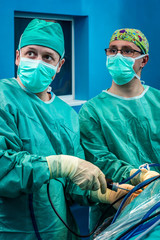 Orthopedic doctors portrait while performing arthroscopic surgery on human patient.