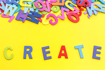 """Colorful wooden alphabet and word """"CREATE"""". Top view on yellow table"""
