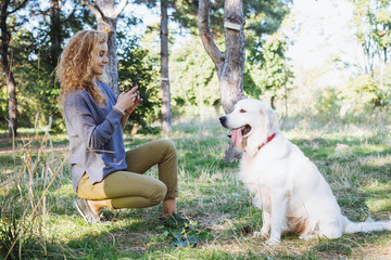 Young female taking photo of labrador retriever dog in park