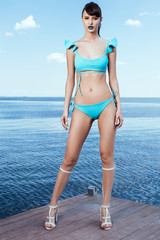Sexy girl in a blue swimwear wearing heels standing on pier over sea horizon. Seductive model on the seaside in Summer. Water background