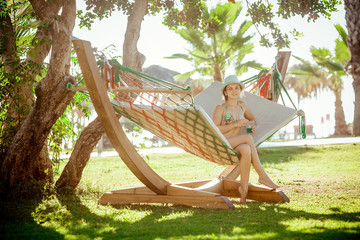 woman with cocktail relaxed in hammock