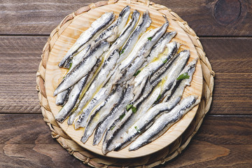 Exquisite marinated anchovies with olive oil and vinegar on wooden table.