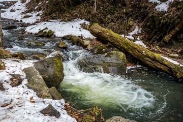 Живописный весенний ручей в Карпатских горах. Таяние снега в начале весны