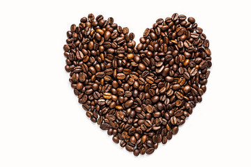 Heart shape made of roasted coffee beans isolated on white background. Close-up coffee beans