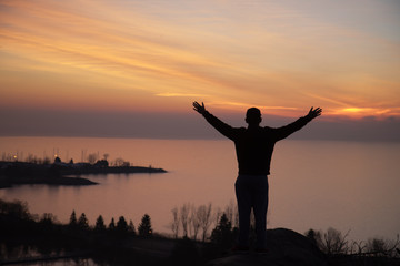 silhouette of man with open arms overlooking water