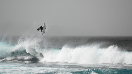 Surfer jumping on a wave