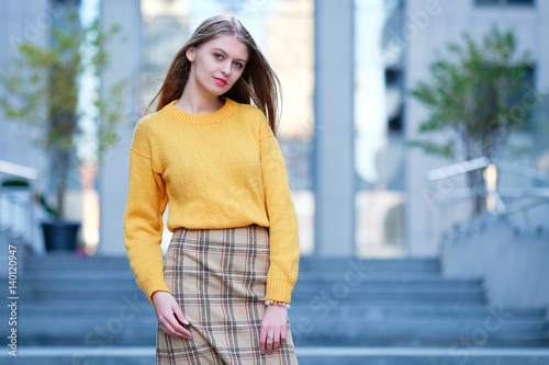 Blond Hair Young Woman In Check Skirt Posing Against Modern Building Business Fashion Style