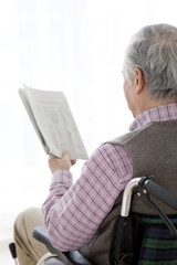 Senior man in wheelchair reading newspaper