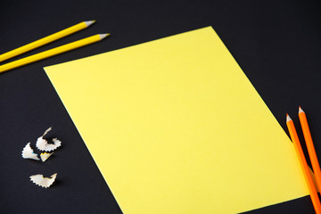 Pencil, shavings and yellow blank paper on dark background, business, design, school, office