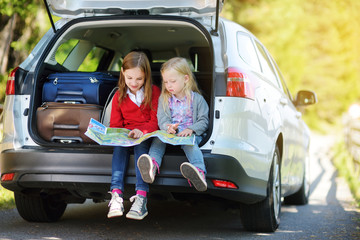 Two adorable little girls ready to go on vacations with their parents. Kids sitting in a car examining a map.
