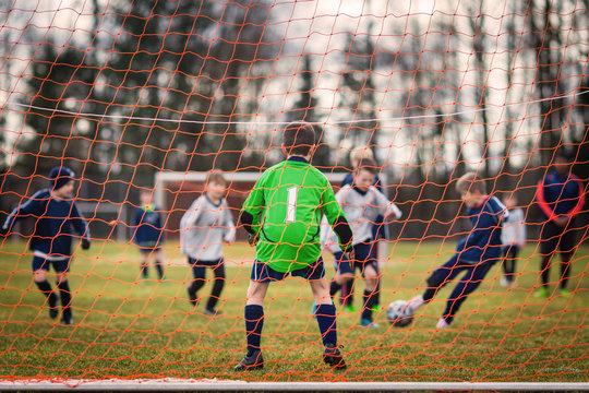 Young soccer goalie defending the net with forward player striking the ball in the background