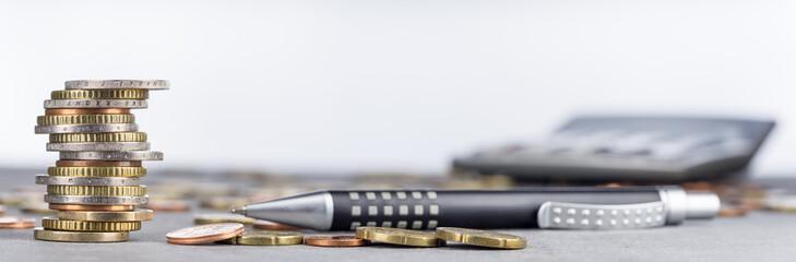 Euromünzen im Stapel und verstreut mit Kugelschreiber, Taschenrechner, Panorama, Hintergrund