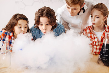 Curious clever children blowing on the chemical fume