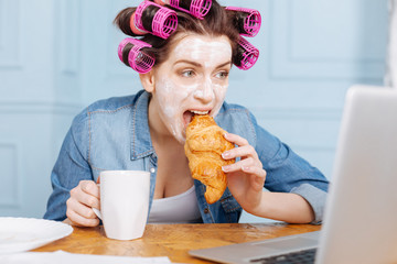 Excited lady watching serial during breakfast