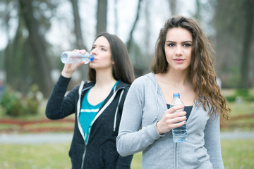 two young woman drinking water in a park