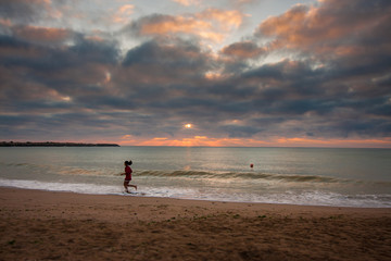 Silhouette of a young girl running along the beach of the sea during an amazing sunrise.