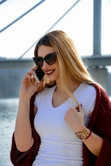 A young woman wearing sunglasses and playing with her hair, while talking on a cell phone.
