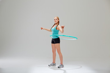 Young fitness girl with hula hoop ring