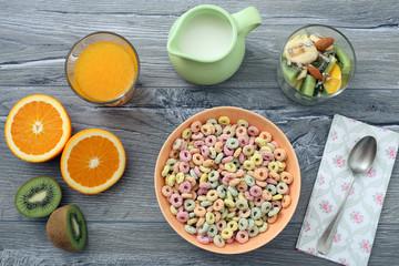 prima colazione con cereali colorati e frutta su tavolo di cucina grigio