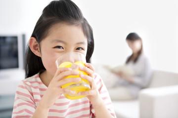 Girl drinking glass of orange juice