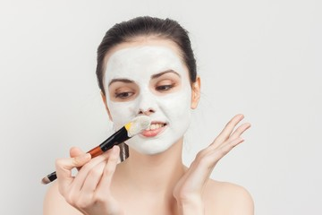 Woman with a sponge in her hands and cream on her face, cotton pads, clean face