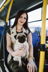 Beautiful young woman sitting in city bus with her pug.