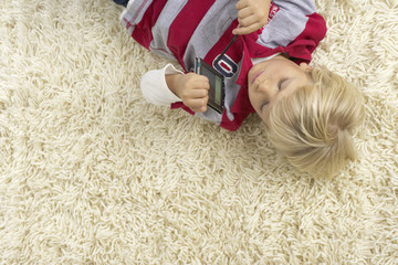 Boy (4-5 Years) lying on a carpet and holding a handheld