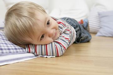 Baby boy lying on pillows on the floor