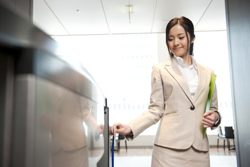 Smiling businesswoman going through security turnstile