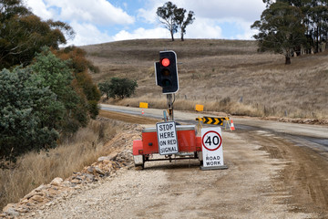 Rural road construction with traffic light and signs