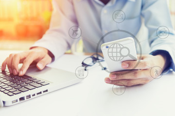 Closeup of business man hand typing on laptop keyboard with mobile phone